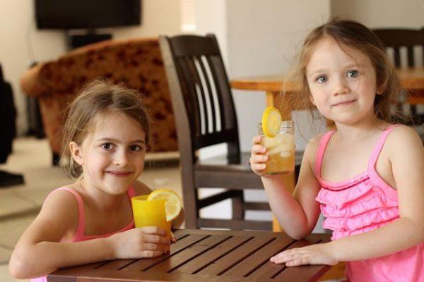 girls in pink dresses holding glasses of lemonade